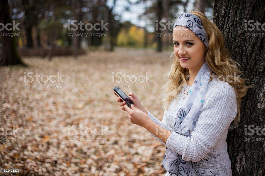 Autumn girl having smartphone conversation in park. stock photo
