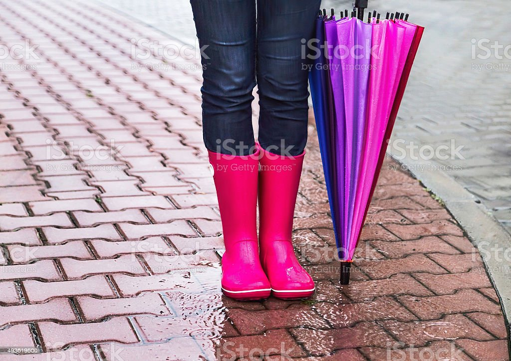 Autumn. Girl wearing rubber boots and has colorful  umbrella.