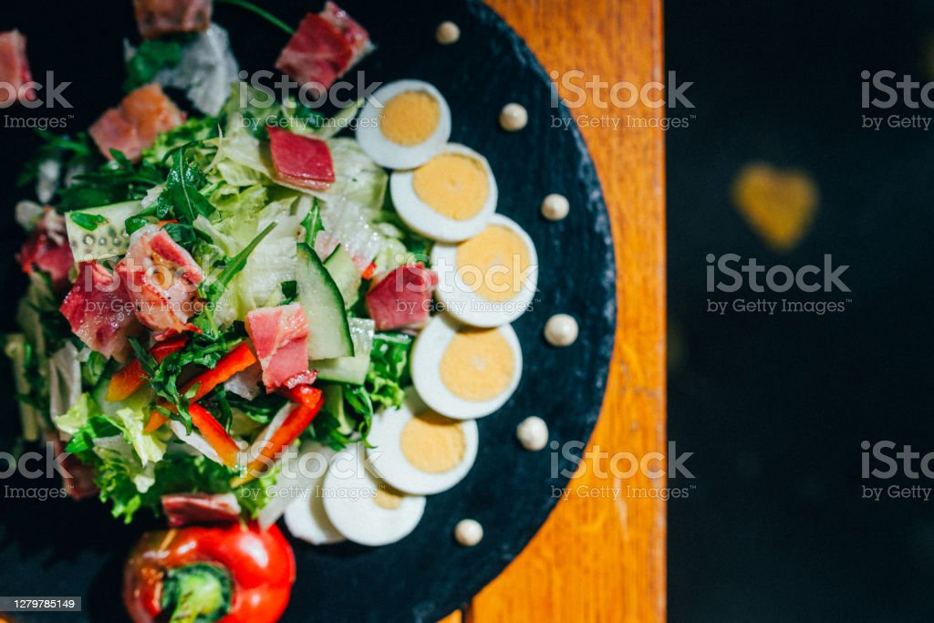 Autumn Green Salad With Eggs Top View of fresh salad with bacon, boiled eggs, fresh pepper, lettuce, cucumber, rocket nicely decorated on a black plate with white salad dressing. Close-up on a decorated plate. Restaurant meal, elegant food composition Macro Antioxidant Stock Photo