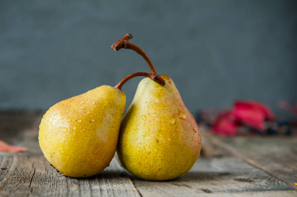 autumn harvest concept -a couple of fresh ripe organic yellow pears with water drops on rustic wooden table, dark stone background. vegetarian, vegan, healthy diet food. selective focus - pera foto e immagini stock
