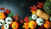 Autumn harvest, diverse assortment of colorful pumpkins on a black marble table counter, top view flat lay.