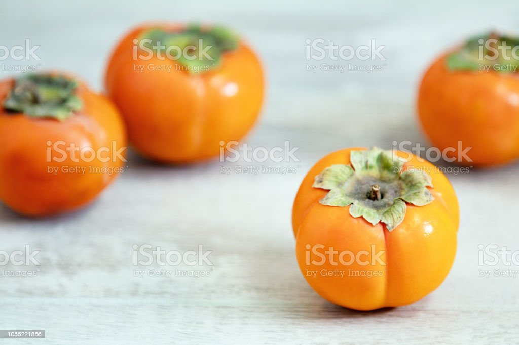 Autumn harvest Persimmon fruits in bowl on a wooden table background stock photo