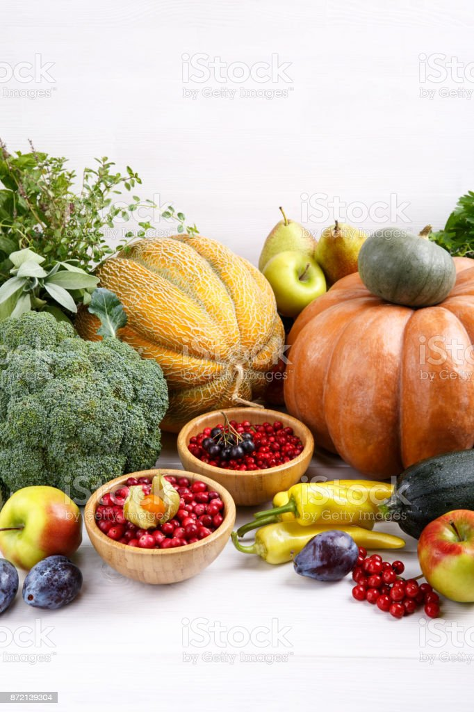 Autumn harvest vegetables, fruits, berries and herbs on white background. Pumpkin, melon, plums, apples, zucchini, pepper, broccoli, pears, chokeberry, viburnum, cranberry, lingonberry, parsley, thyme, sage. stock photo