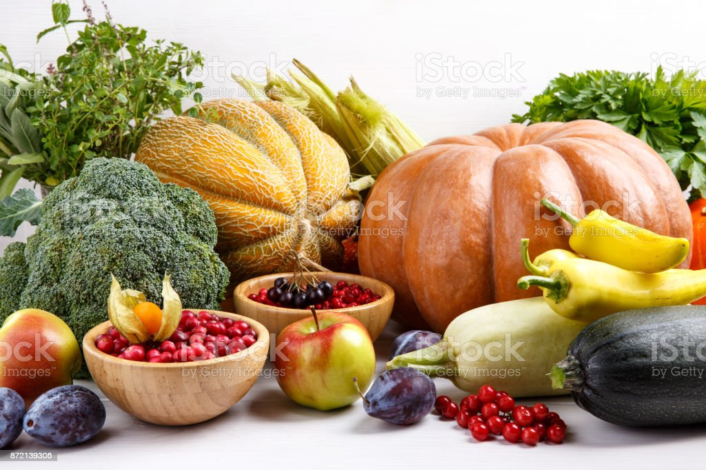 Autumn harvest vegetables, fruits, berries and herbs on white background. Pumpkin, melon, plums, apples, zucchini, pepper, broccoli, corn, chokeberry,  cranberry, lingonberry, viburnum, parsley, thyme, sage. stock photo