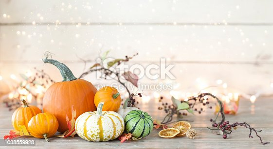 istock Autumn holiday pumpkin arrangement against an old white wood background 1038559928