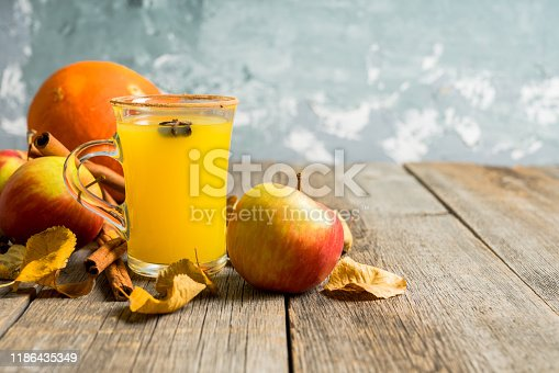 578566044 istock photo Autumn hot and spicy drink with pumpkin and orange juice on the rustic background 1186435349