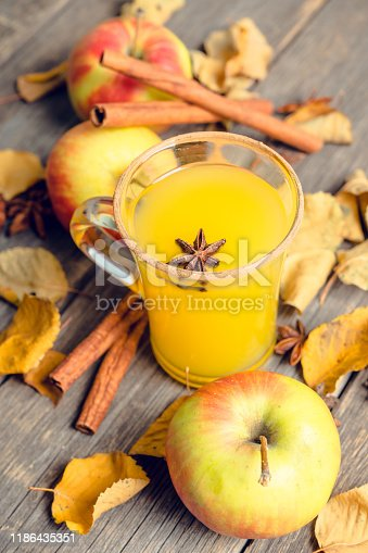 578566044 istock photo Autumn hot and spicy drink with pumpkin and orange juice on the rustic background 1186435351