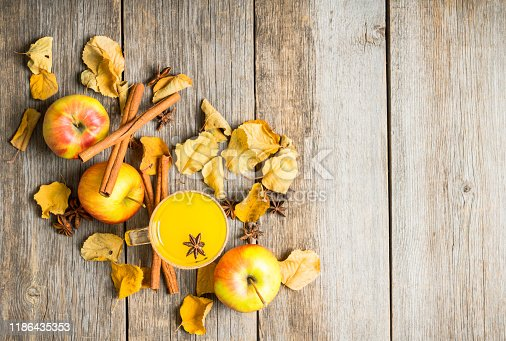 578566044 istock photo Autumn hot and spicy drink with pumpkin and orange juice on the rustic background 1186435353