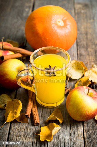 578566044 istock photo Autumn hot and spicy drink with pumpkin and orange juice on the rustic background 1186435358