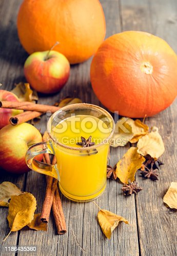 578566044 istock photo Autumn hot and spicy drink with pumpkin and orange juice on the rustic background 1186435360