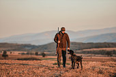 Young man hunting with german wirehaired pointer. The best friends.
