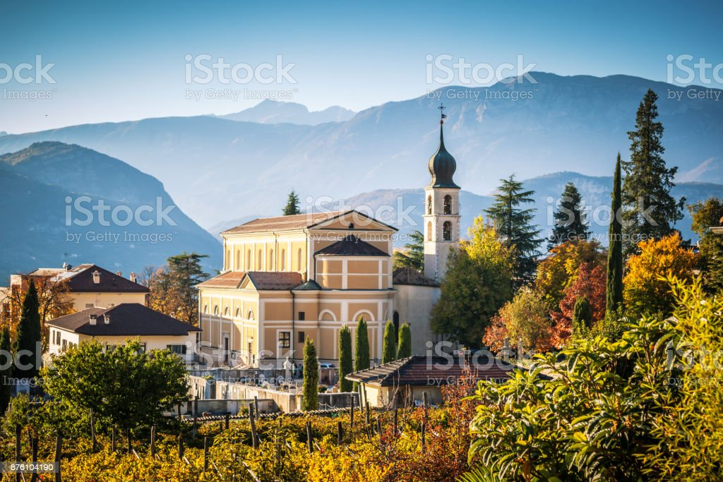 Autumn in Alps with church in Trento Beautiful autumnal landscape with church and Alps in Trento, the Northern Italy Alto Adige - Italy Stock Photo
