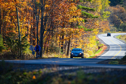 Autumn in Canada - the curved country road eautiful with vehicles along with the autumn scene in Ontario Province.