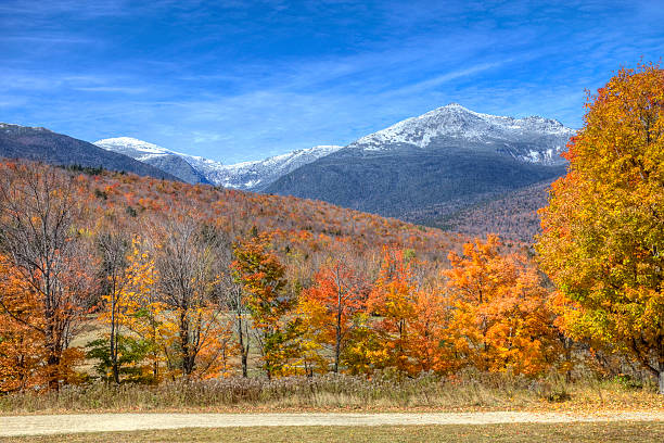 Autumn in New Hampshire Snowcapped mountains in the White Mountains National Forest in New Hampshire during the autumn foliage seasonMore Autumn scenes mount washington new hampshire stock pictures, royalty-free photos & images