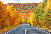 Scenic Autumn Road in the Adirondacks region of New York. The Adirondack Mountains form a massif in northeastern New York, United States