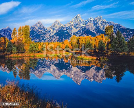 Overflow from the Snake River reflects the autumn colors of cottonwood trees and the Grand Teton Range, WY