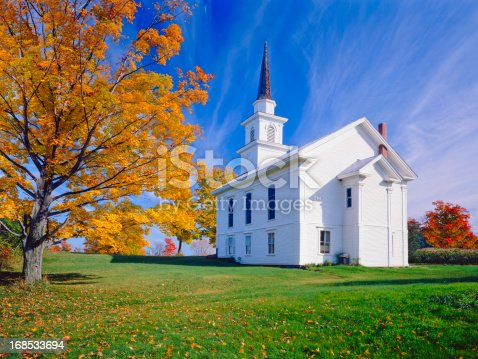 Autumn sugar maple and country church in Vermont