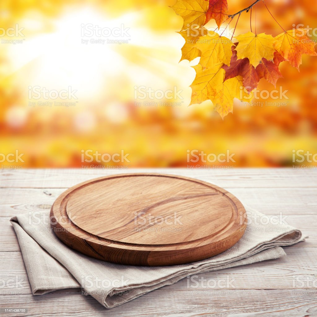 Autumn landscape and Pizza board with napkin on white wooden table....
