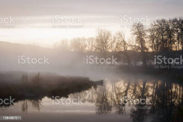 Photo of Autumn landscape fog over river and sky with rising sun