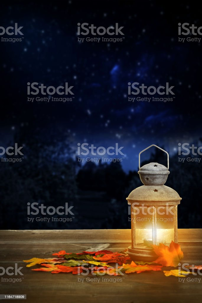 autumn lantern on wood table at night with fall leaves
