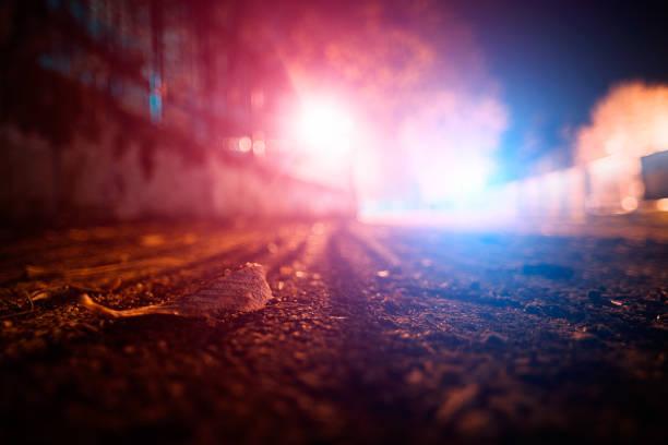 herfst blad op het wegdek met blauwe en rode politie verlichting op de achtergrond - criminaliteit stockfoto's en -beelden