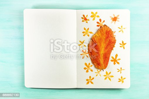 istock Autumn leaf taped to notebook page with watercolor drawings 688862130