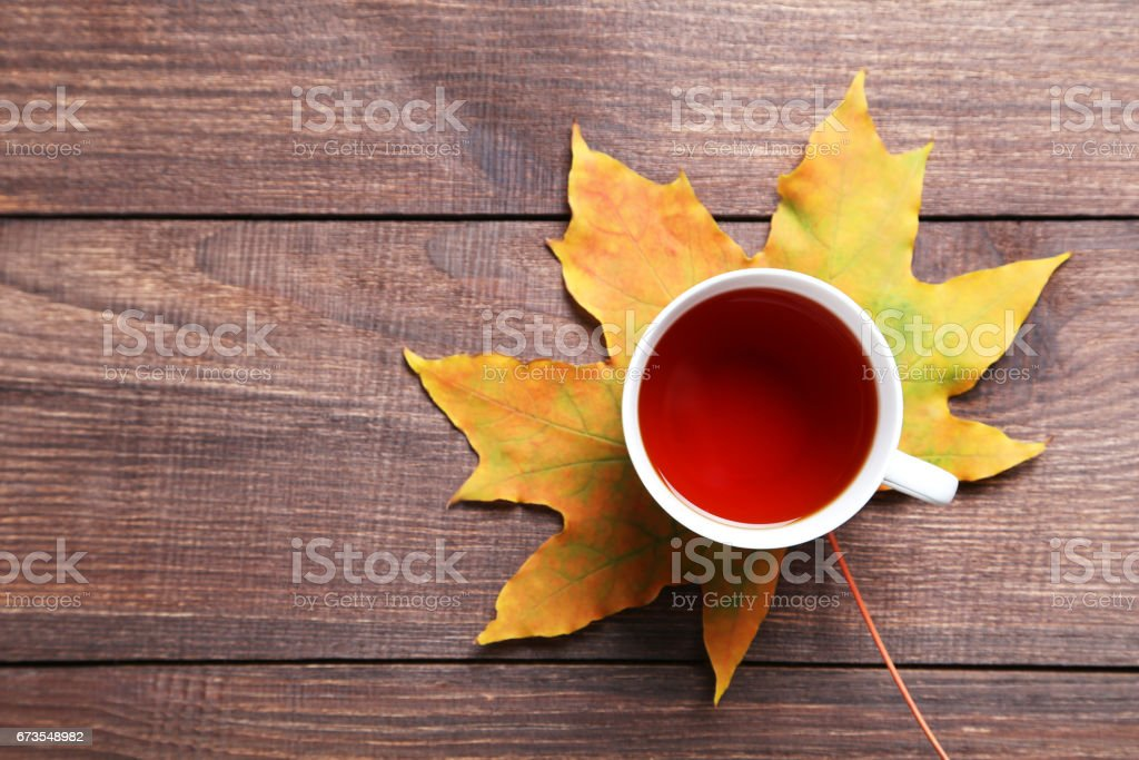 Autumn leaf with cup of tea on brown wooden table royalty-free stock photo