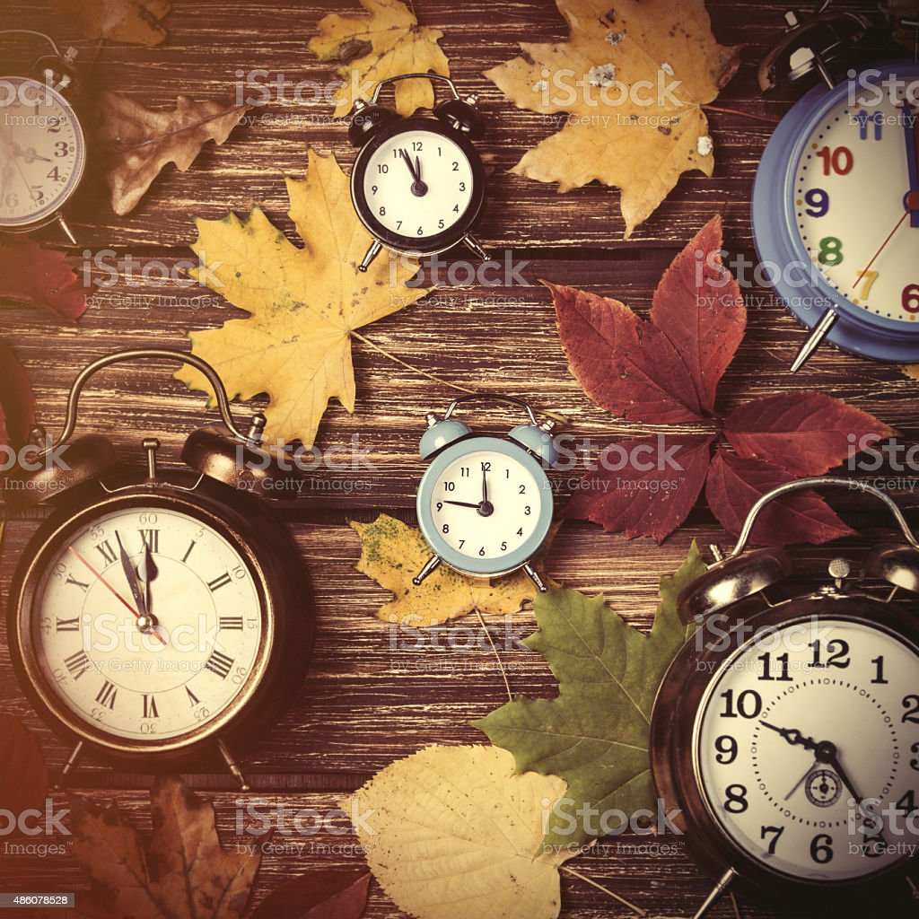Autumn leafs and alarm clock on wooden table. stock photo