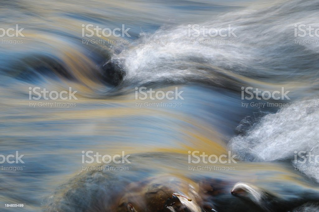 Autumn leaves and blue sky reflected in stream ripples stock photo