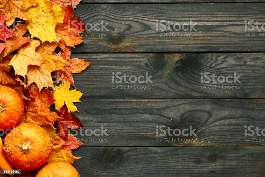 Autumn leaves and pumpkins over old wooden background stock photo