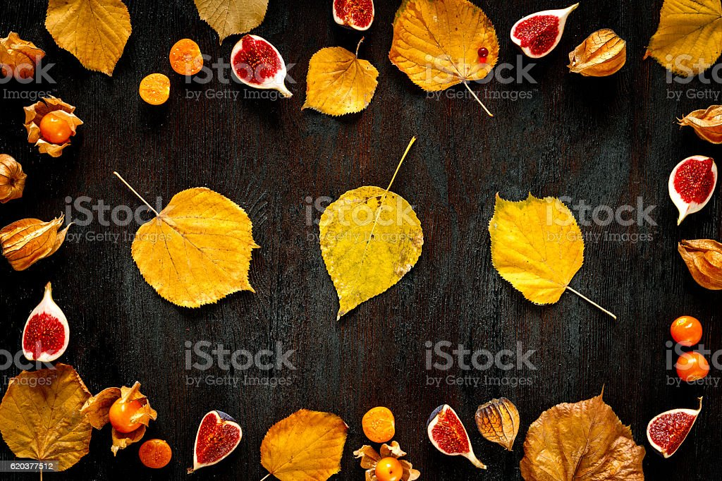 autumn leaves and sliced fruit on wooden background top view zbiór zdjęć royalty-free
