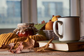Autumn leaves, cup of coffee, warm scarf, fruits basket and book with glasses on the table. Old wooden table by the window in the autumn beautiful day, close-up