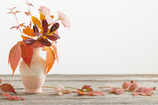 autumn leaves in vase on wooden table