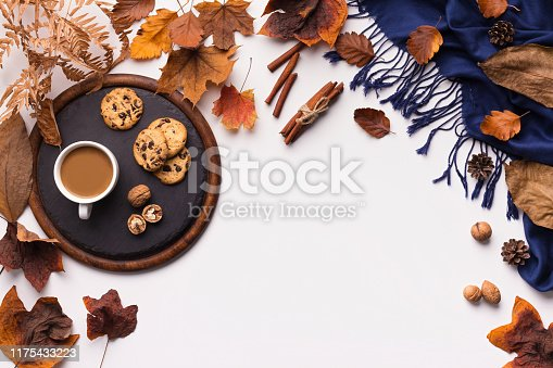 istock Autumn leaves pattern, coffee and blue warm scarf on white 1175433223
