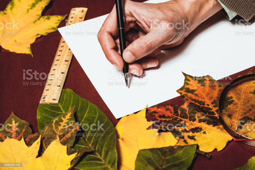 hand holds a pen over a sheet of white paper on a brown table. Nearby...