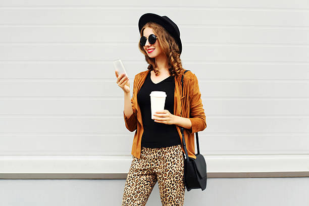 Autumn luxury pretty woman, coffee cup, smartphone walking in city stock photo