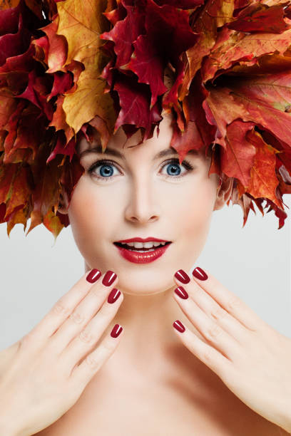 Autumn Makeup. Beautiful Woman with Fashion Makeup, Manicure Hands and Fall Leaves Wreath. Face Closeup stock photo