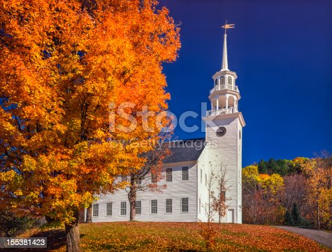 autumn maple trees frame New England Village Square and 19th century Town Hall, which looks like a church building. Stratford Vermont.