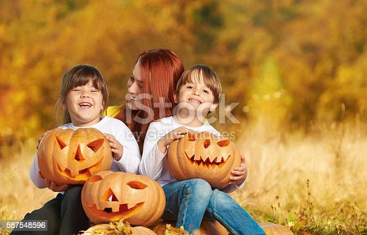 happy family in great autumn day smiling, enjoying time in nature and holding Halloween pumpkins.