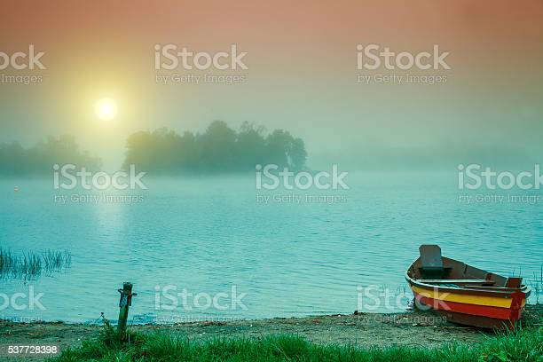 Photo of Autumn misty early morning. Wooden boat on the river bank