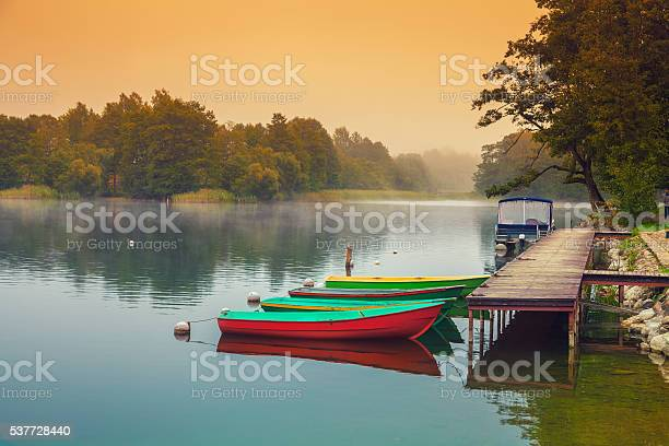 Photo of Autumn misty early morning. Wooden boats at the river bank