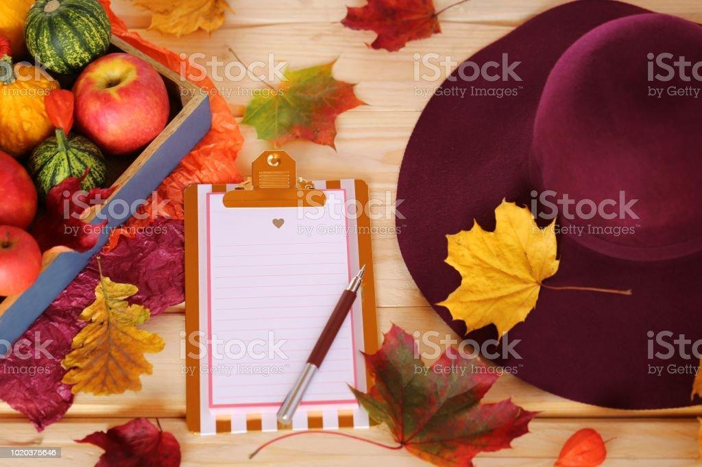 Maquette de l'automne. presse-papiers avec les potirons, les pommes, les feuilles d'érable jaune et chapeau de Bourgogne sur une vue de table.top en bois, espace copie. Saison d'automne. Temps de l'automne - Photo