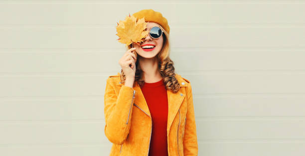 Autumn mood! happy smiling woman holding in her hands yellow maple leaves hiding her eye over gray wall background stock photo