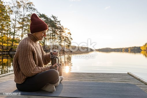 A woman sitting by a lake in a forest during autumn. She is drinking tea out of a travel mug and is wearing a knitted hat and sweater.