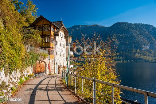 Autumn morning scenery on Hallstattersee with picturesque house, lake and walkway illuminated by rising sun. Hallstatt, Salzkammergut region, Upper Austria