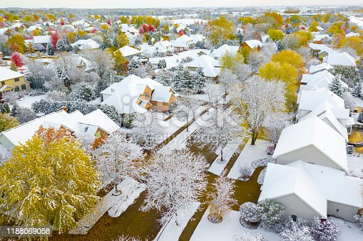 Autumn neighborhood under fresh snow, trees ablaze with fall colors.