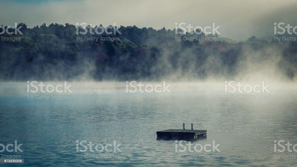 Otoño en un lago con un muelle flotante - foto de stock