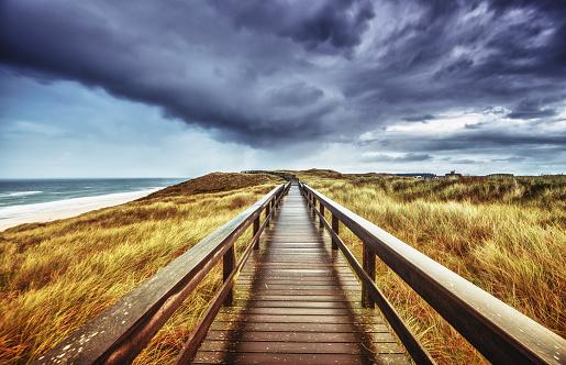 Autumn on Sylt - Wooden path under dramatic sky