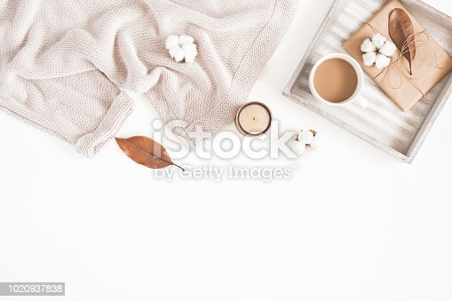 istock Autumn or winter composition. Cup of coffee, gift, dried autumn leaves, beige sweater on white background. Flat lay, top view, copy space 1020937838