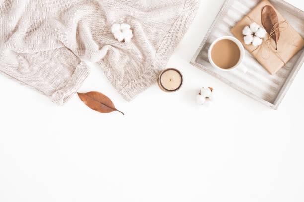 herbst oder winter zusammensetzung. tasse kaffee, geschenk, getrocknete herbst blätter, beige pullover auf weißem hintergrund. flach legen, top aussicht, textfreiraum - herbst kerzen stock-fotos und bilder